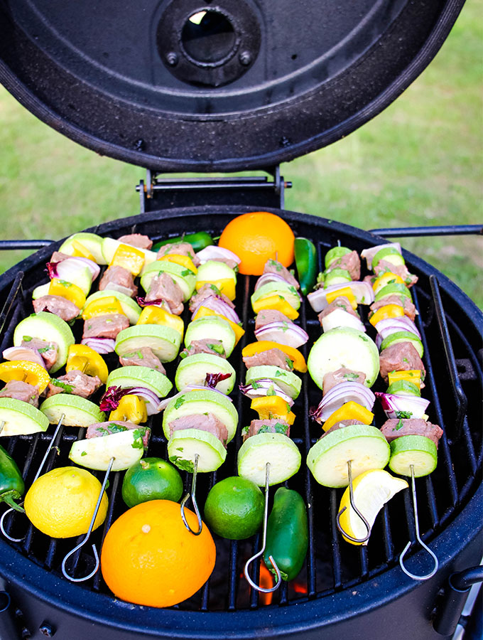 Grilled Carne Asada Kabobs are placed on the grill with jalapeños and citrus fruits.