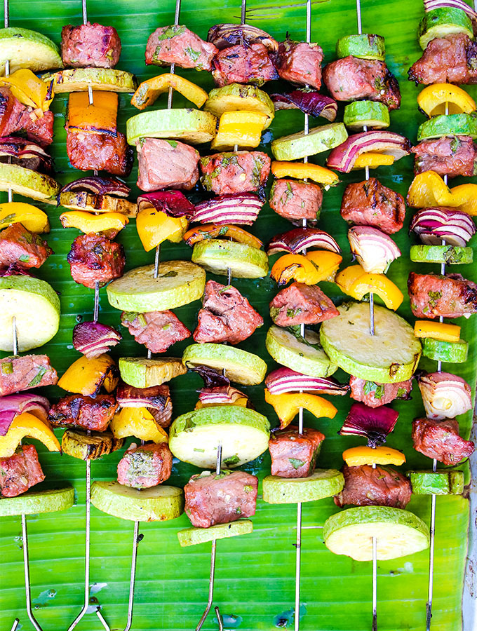 Grilled Carne Asada Kabobs are grilled and placed on a banana leaf.