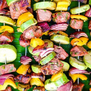 Grilled Carne Asada Kabobs are grilled and stacked on top of a banana leaf.