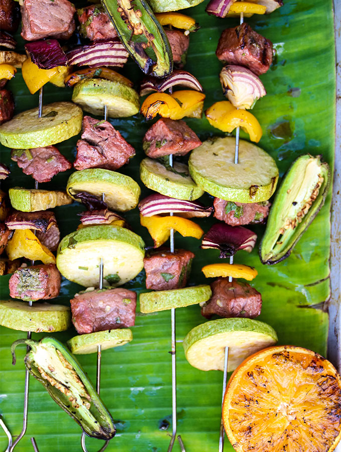 Grilled Carne Asada Kabobs are grilled and displayed on a banana leaf.