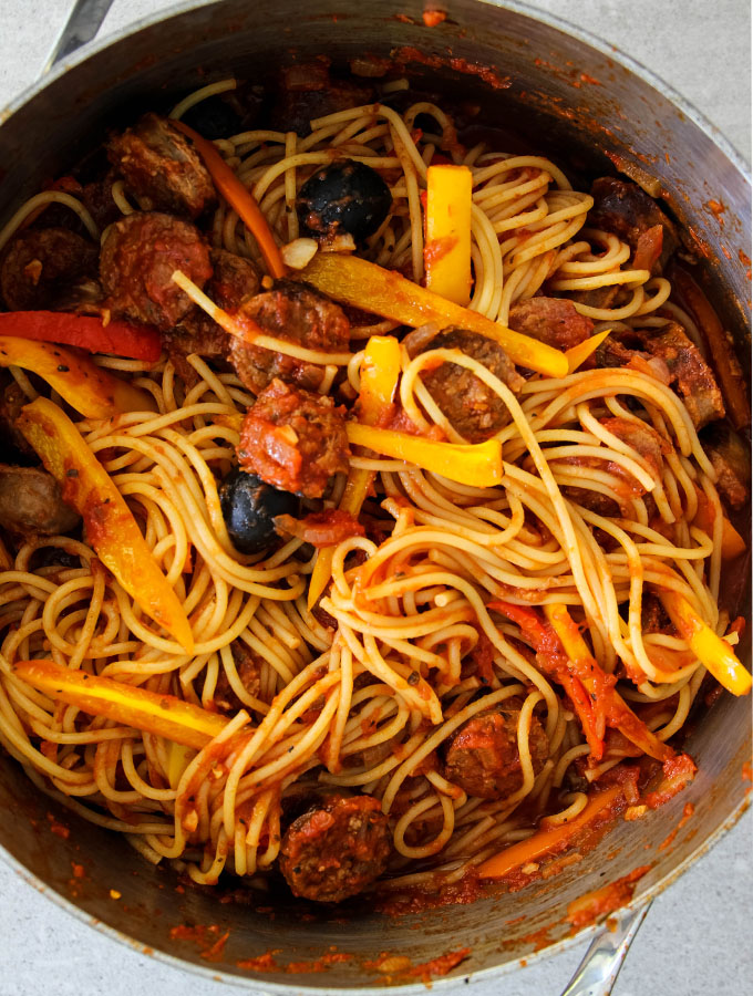 Hot Sausage and Pepper Pasta is tossed in a large pot with black olives.