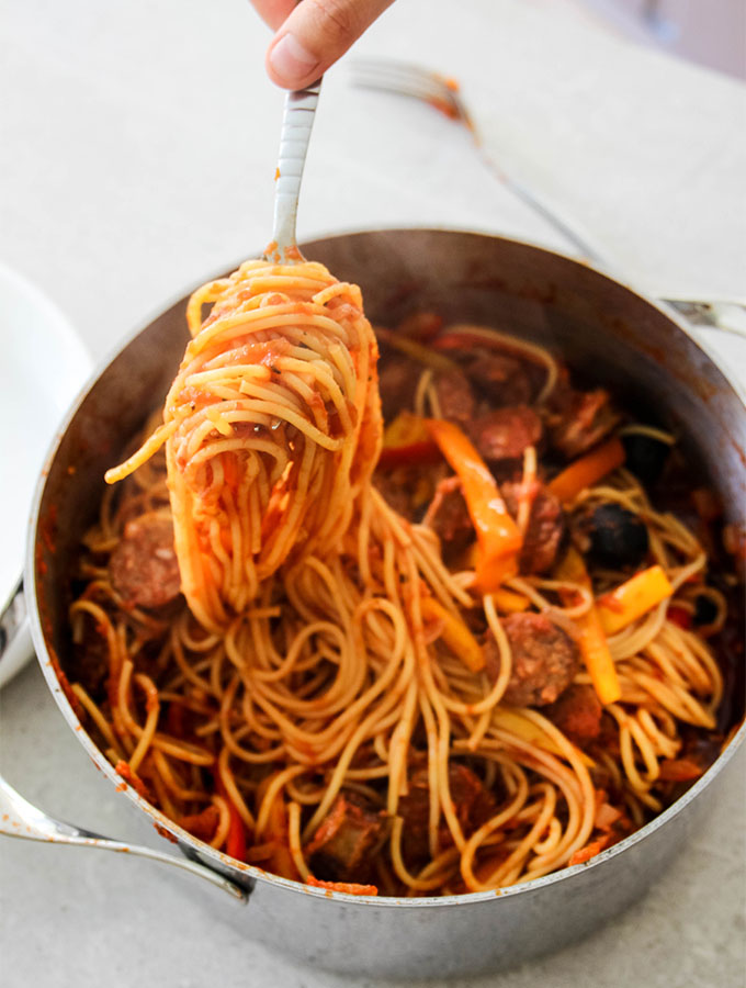 Hot Sausage and Pepper Pasta tossed in a large metal pot.