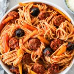 Hot Sausage and Pepper Pasta is plated in a white bowl next to a bowl of parmesan cheese.
