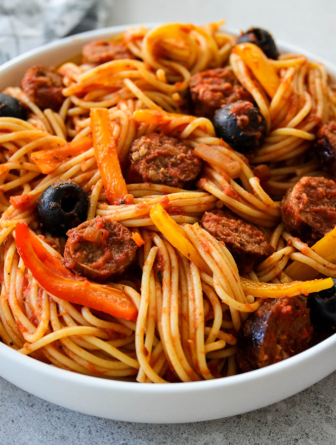 Hot Sausage and Pepper Pasta is plated in a white bowl with large black olives.