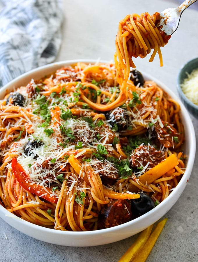 Hot Sausage and Pepper Pasta is plated in a white bowl with a fork of twirled pasta.