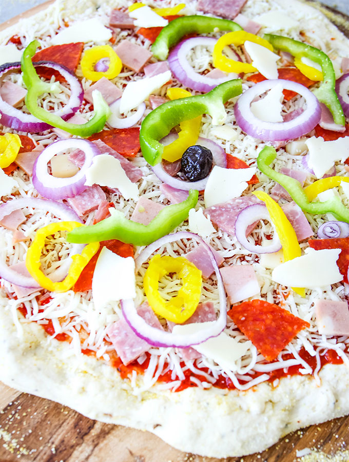 Italian Sub Pizza Is topped with all the toppings on a pizza pan.