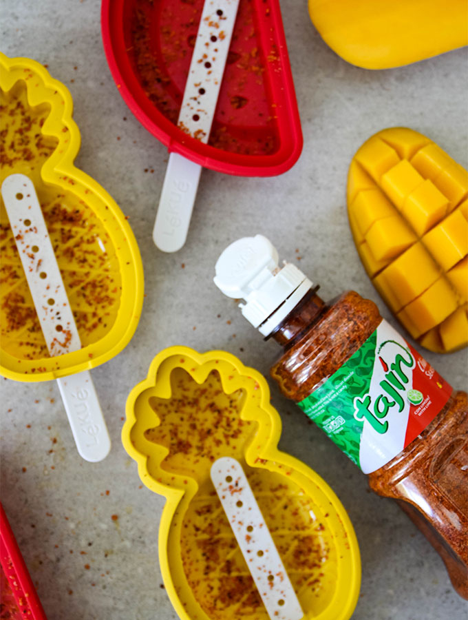 Tajin seasoning is sprinkled on popsicle molds before they are put in the freezer.