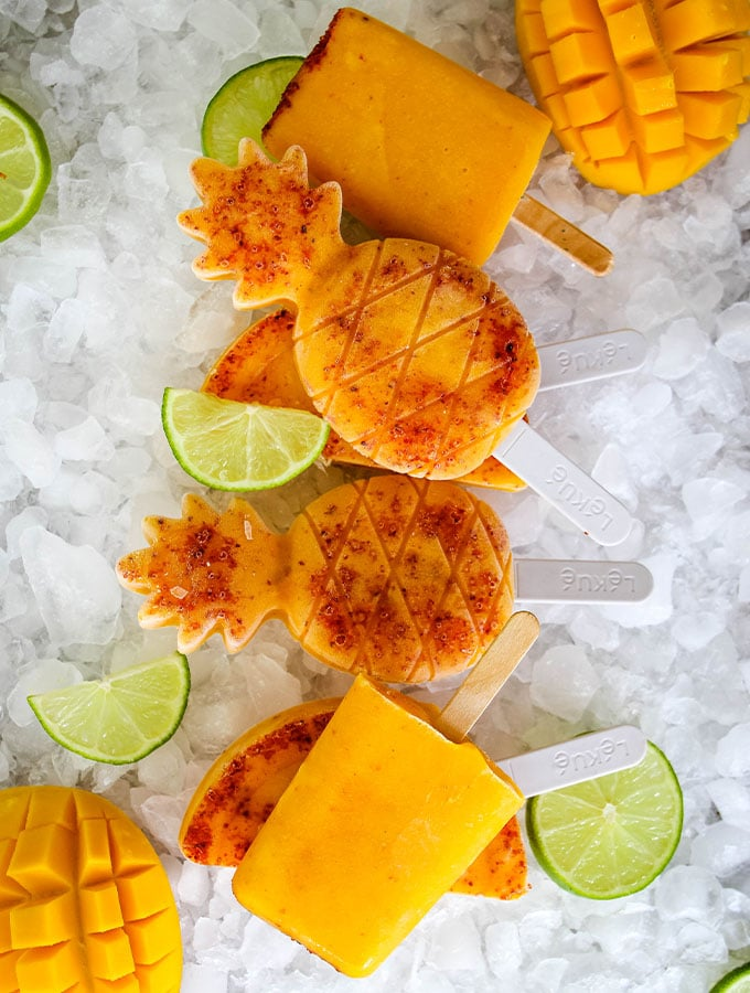 Mango and Tajin paletas are plated on top of ice and stacked.