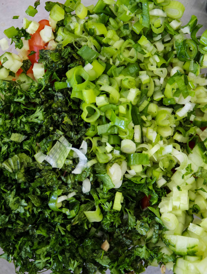 Fresh herbs are chopped in preparation for 15 Minute Summer Tabouli Orzo Pasta Salad.