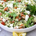 Summer Tabouli Orzo Pasta Salad is plated and topped with lemon wedges.