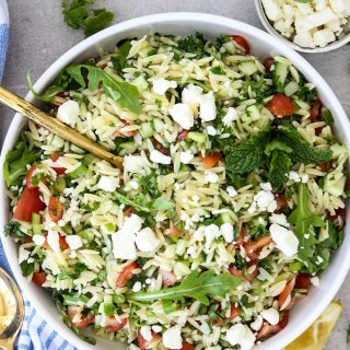 Summer Tabouli Orzo Pasta Salad is plated in a white bowl and topped with feta cheese.