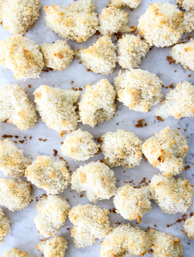 Cauliflower is breaded and plated on a baking sheet, then baked.