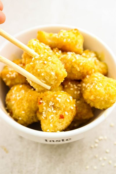 Baked Orange Cauliflower is plated and chop sticks are holding a bite.