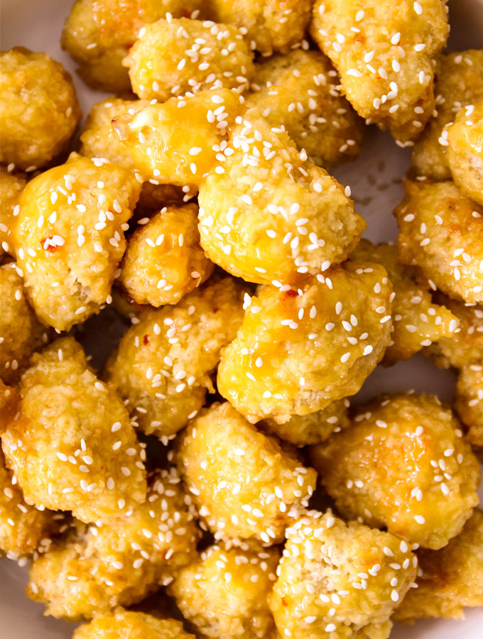Baked Orange Cauliflower is plated and sprinkled with sesame seeds.