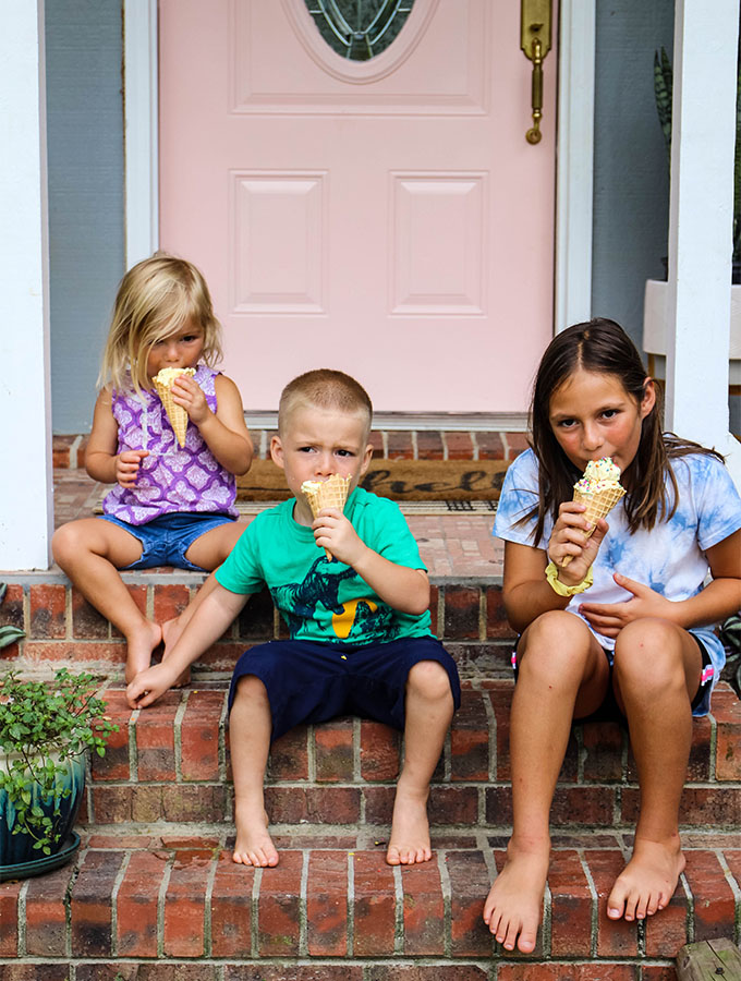 Sherry's kids are sitting on the front porch eating ice cream cones.