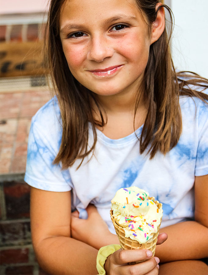Ava is eating a waffle cone stacked with No Churn Cake Batter Ice Cream.