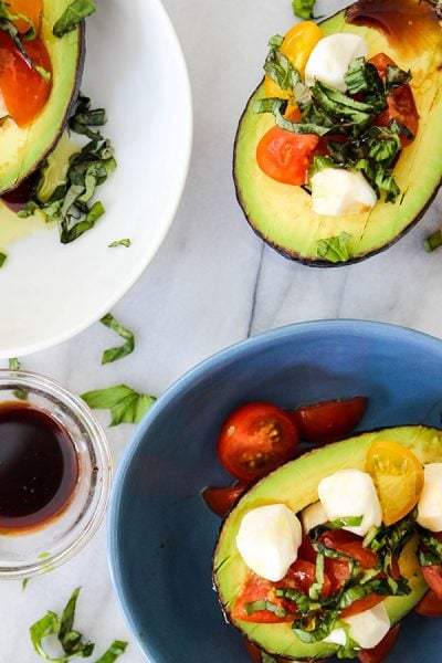 5 Minute Caprese Stuffed Avocados are plated together with a bowl of balsamic vinegar.