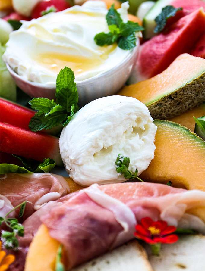 Burrata cheese is sliced open to show the cream texture on the Italian Summer Melon and Cheese Board.