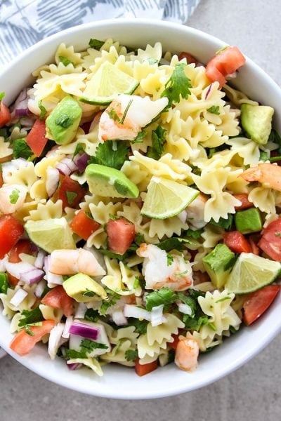 Shrimp Ceviche Pasta Salad is plated in a white bowl and topped with wedged of lime.
