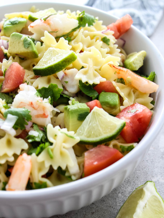 Shrimp Ceviche Pasta Salad is plated in a white bowl and topped with lime wedges.