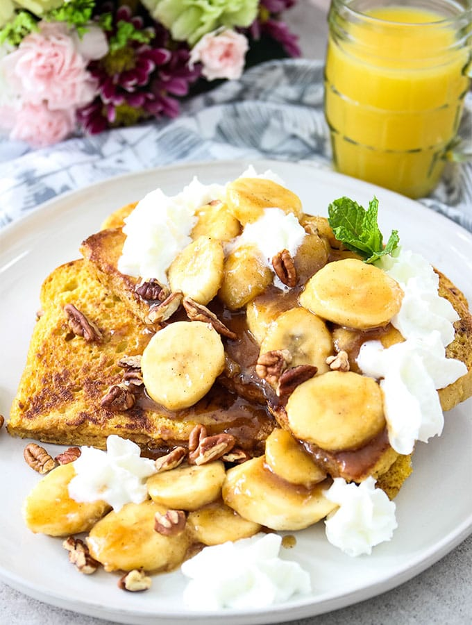 Banana Foster French Toast is plated with orange juice. pecans, and whipped cream.