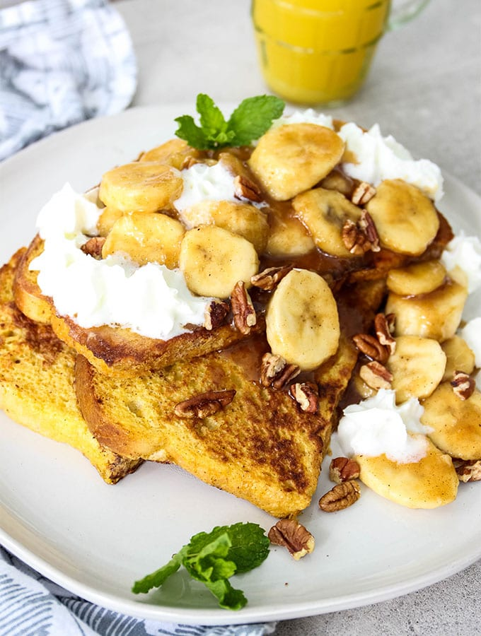 Banana Foster French Toast is plated and served with a glass of orange juice.
