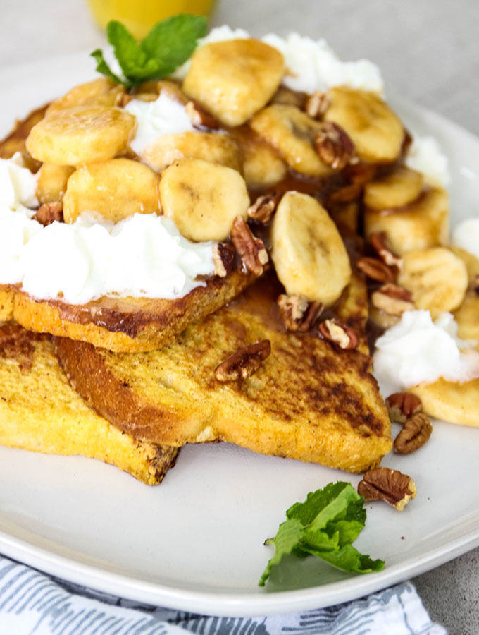 Banana Foster French Toast is plated and topped with whipped cream and pecans.