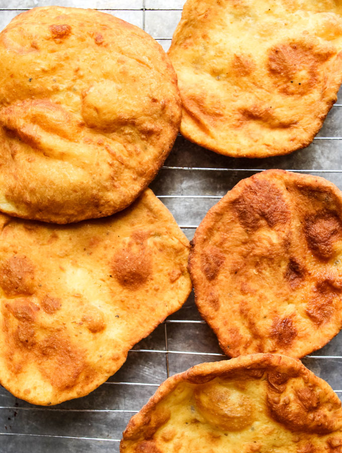 Deep Fried Neapolitan Pizza discs are fried, then laid on a cooling rack to cool.