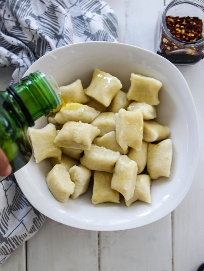 Homemade Italian Gnocchi is drizzled with olive oil and topped with red pepper flakes.