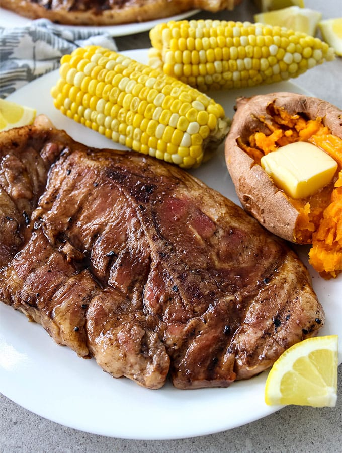 Grilled Sweet Tea Pork Chops is plated with sweet potato and corn on the cob.