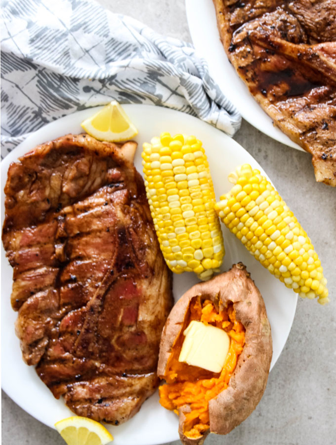 Grilled Sweet Tea Pork Chops are plated with a sweet potato and corn on the cob.