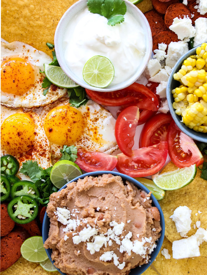 Mexican Tostada Breakfast Board is served with refried beans and sour cream.