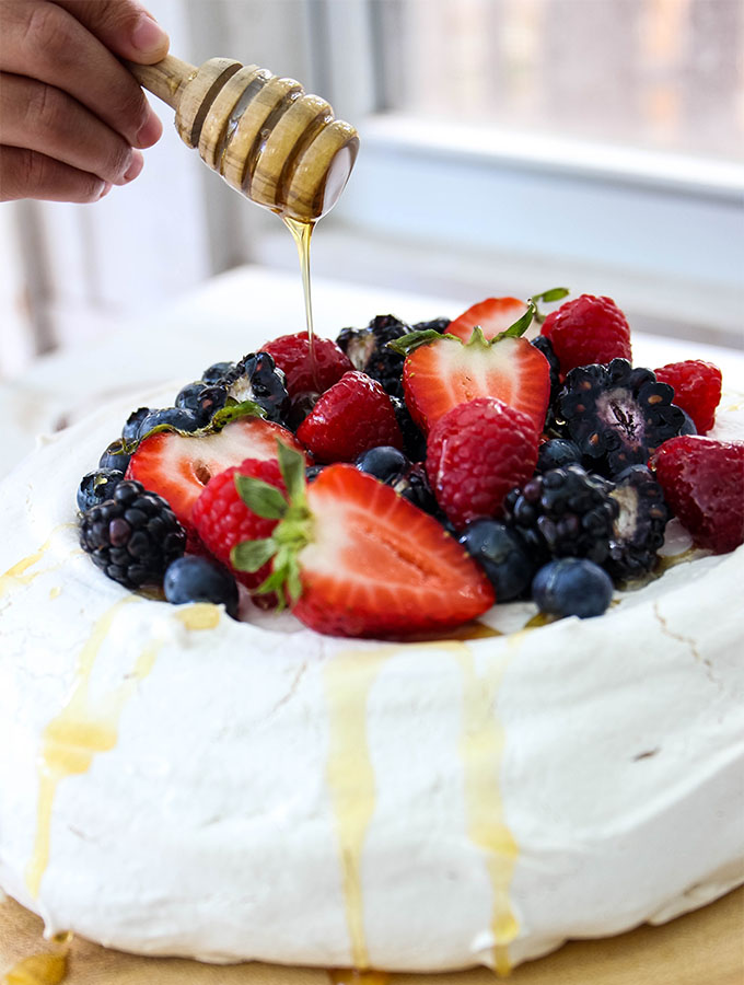 Fresh Berry Pavlova is topped with honey from a honey swizzle stick.