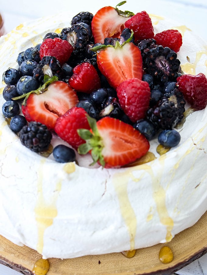 Fresh Berry Pavlova is topped with cut berries and topped with honey.