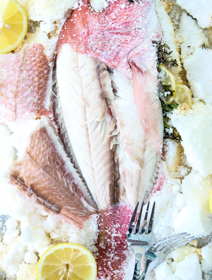 Salt Crusted Fish is displayed with lemon wedges and forks.