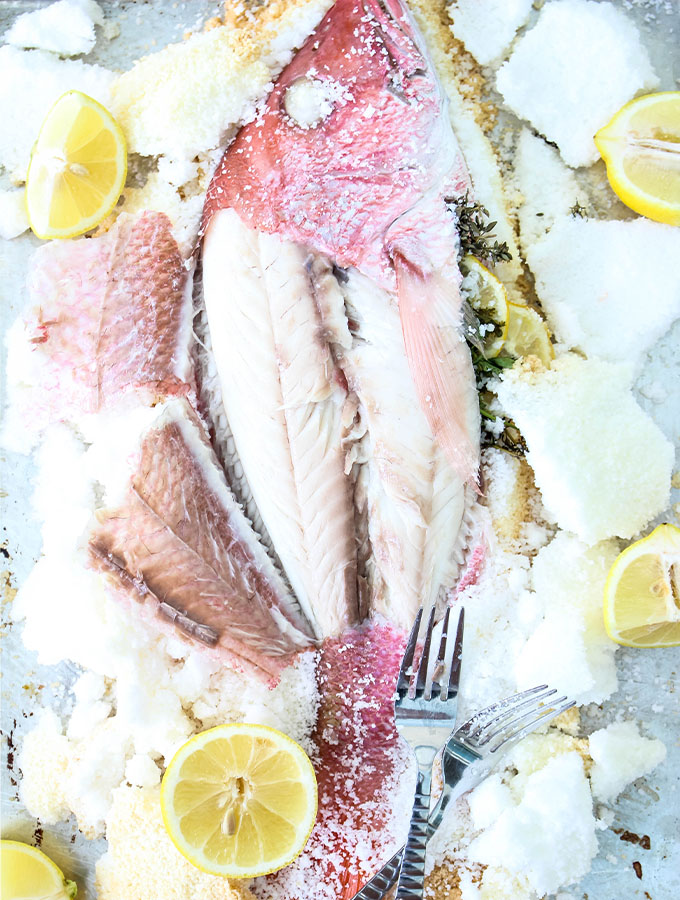Salt Crusted Fish is baked on a baking sheet and served with lemon wedges.
