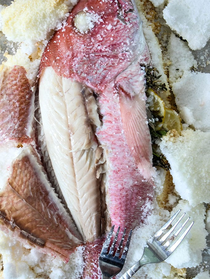 The fish skin is peeled back to expose the Salt Crusted Fish meat.