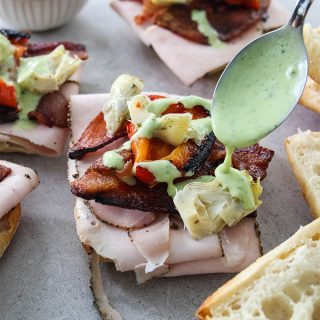 Turkey and Bacon Sandwiches are being topped with a spoonful of basil aioli.