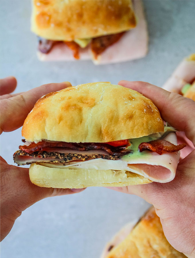 Turkey and Bacon Sandwich with Basil Aioli is held with two hands.