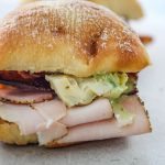 Turkey and Bacon Sandwich with Basil Aioli is plated for a close up shot.