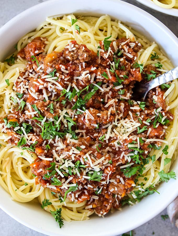Bolognese Sauce is on top of spaghetti pasta with parmesan cheese.
