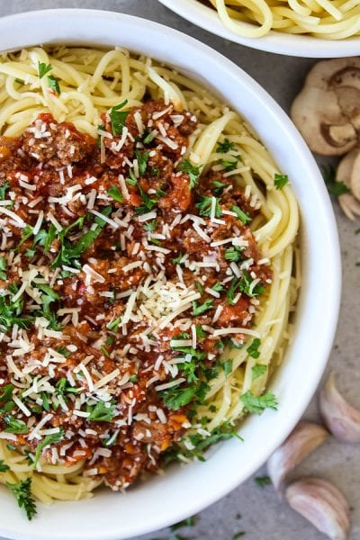Authentic Bolognese Sauce is placed on top of spaghetti in a white bowl.