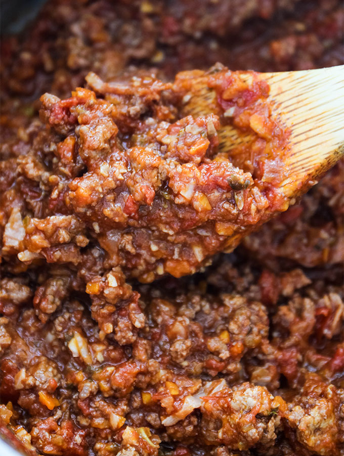 A spoon is stirring Authentic Bolognese Sauce to show texture.