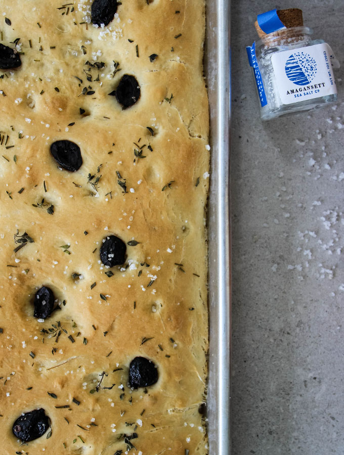 Easy Olive and Herb Focaccia is topped with coarse sea salt.