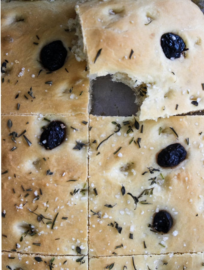 Easy Olive and Herb Focaccia is cut and taken a bite out of.