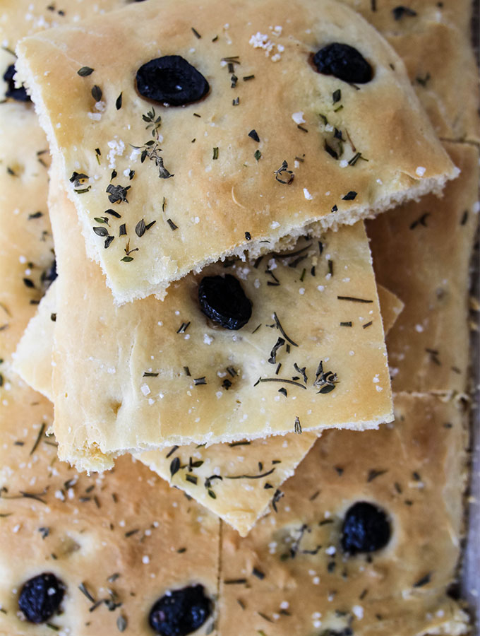 Easy Olive and Herb Focaccia is stacked to show the fresh herbs and coarse sea salt tops.
