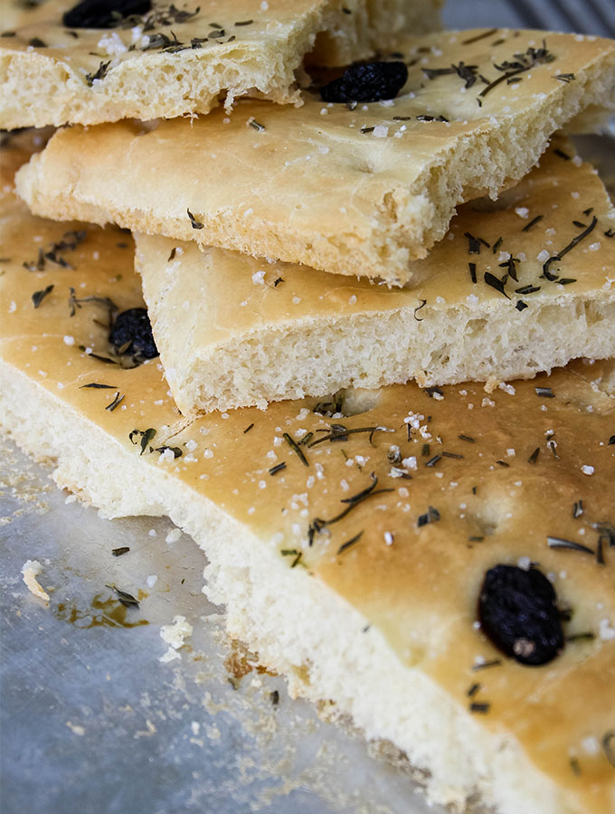 Easy Olive and Herb Focaccia is stacked to show the texture.