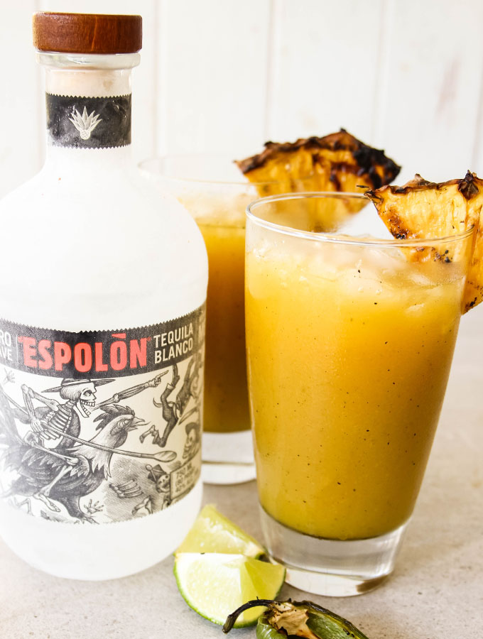 A frosty bottle of tequila is placed next to cups of Grilled Pineapple Jalapeño Margaritas.