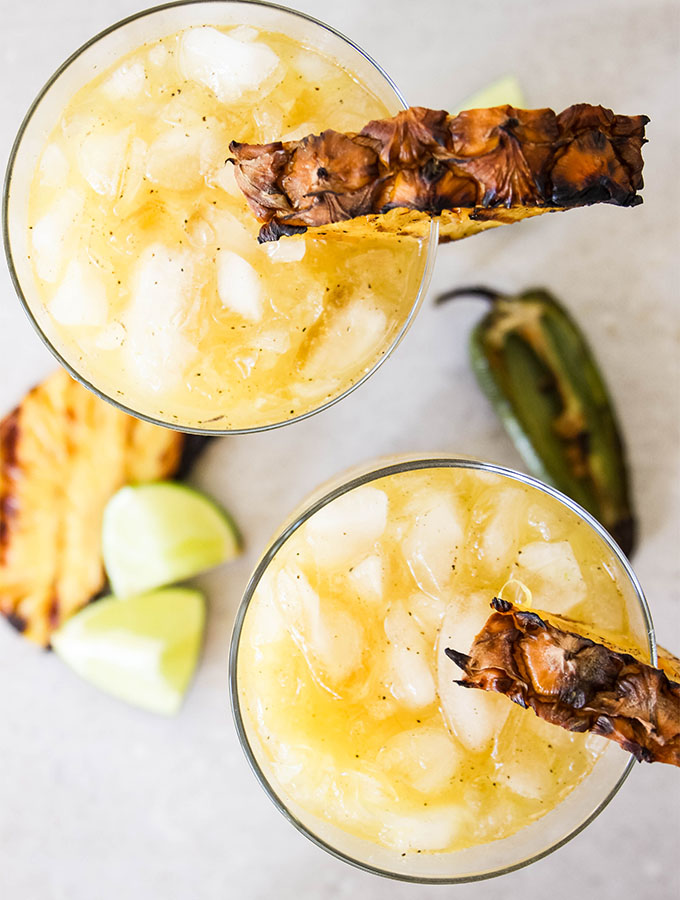 Grilled Pineapple Jalapeño Margaritas are topped with ice and a garnish.