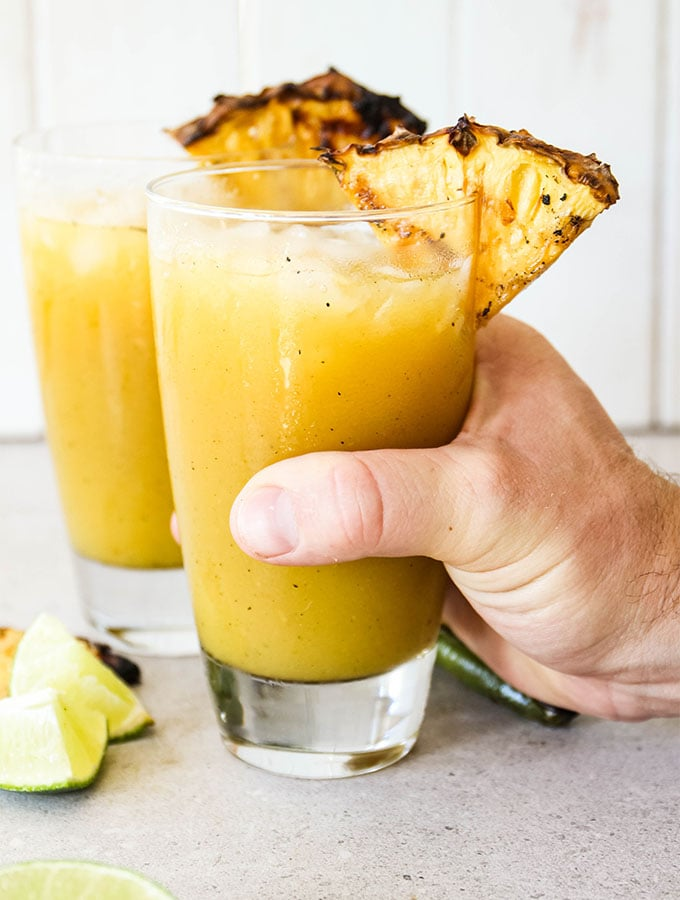 A hand is grabbing a glass of Grilled Pineapple Jalapeño Margaritas.